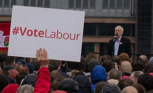 "Jeremy Corbyn addressing a crowd, prominent ""vote labour sign"" in foreground."