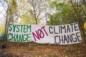 "Sheets arranged as signs with ""System Change Not Climate Change"" written on them"